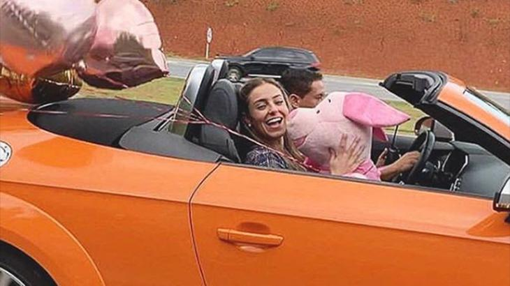 Paula em carro conversível laranja