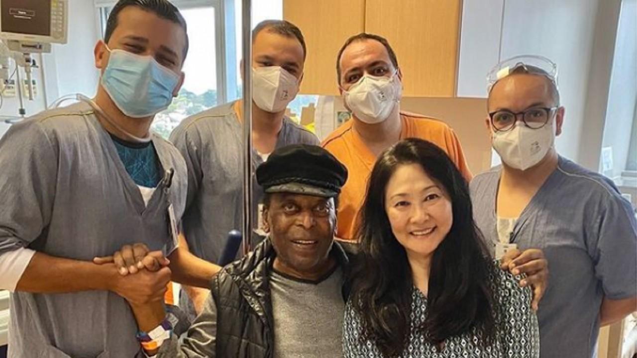 Pelé posa para foto, sentado, com equipe médica ao seu lado