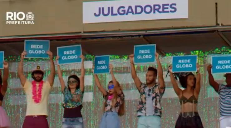 """Trecho do vídeo mostra dramatização de supostos jurados na Marquês de Sapucaí, com todos segurando cartazes escritos """"Rede Globo"""""""