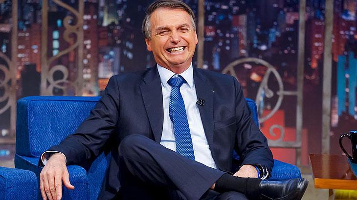 Jair Bolsonaro sentado numa poltrona e rindo