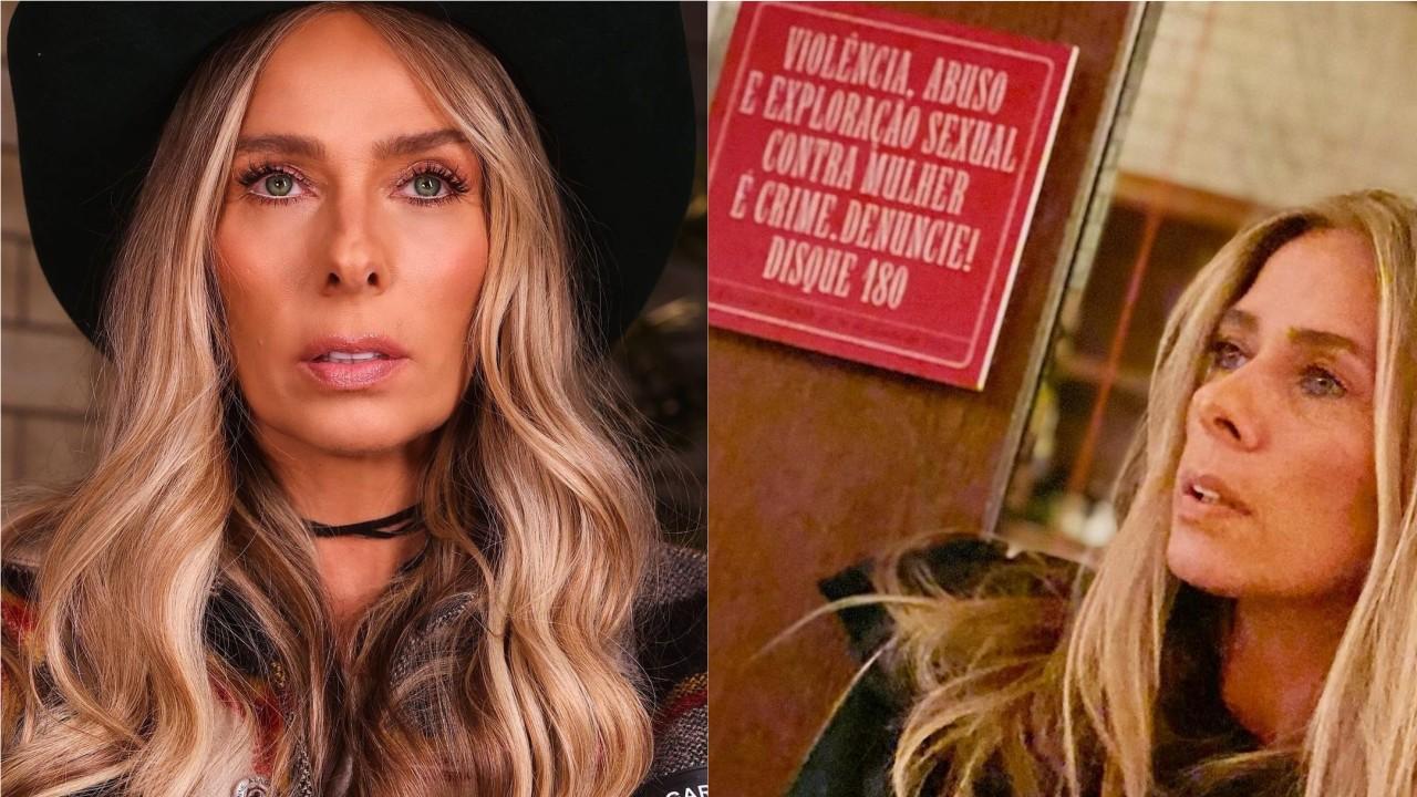 Adriane Galisteu, apresentadora de A Fazenda 2021, posa perto de um aviso que condena violência contra mulheres