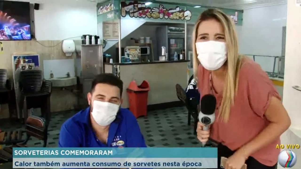 Repórter (com microfone na mão) e entrevistado (sentado à mesa) riem em sorveteria