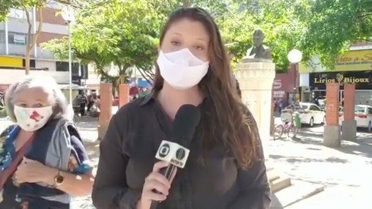 Repórter gravando matéria sendo observada por idosa