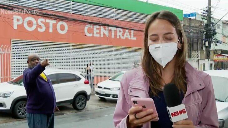 Homem gritando apontando dedo para repórter, que segura o microfone e celular