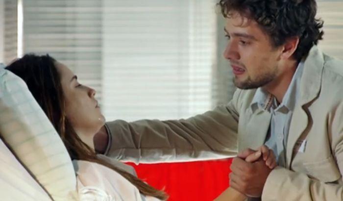 Rodrigo se inclina na direção de Ana, deitada, e segura a mão dela