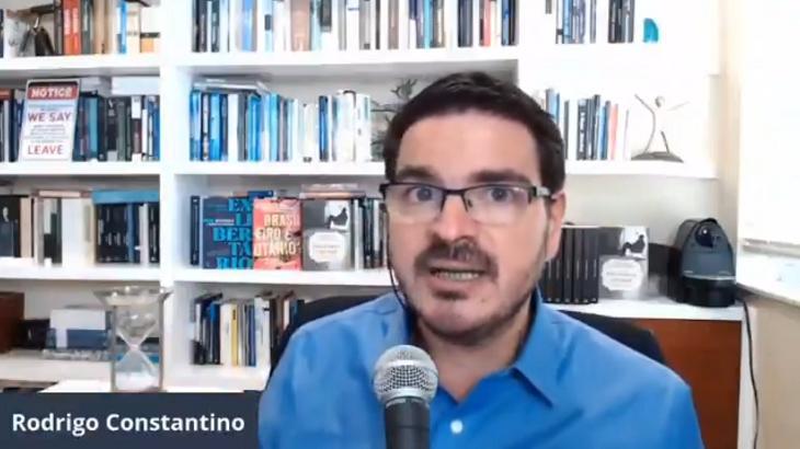 Rodrigo Constantino sentado e falando perto de um microfone