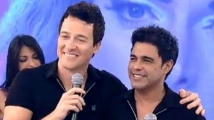 Rodrigo Faro de microfone na mão abraçado com Zezé di Camargo no palco do Hora do Faro