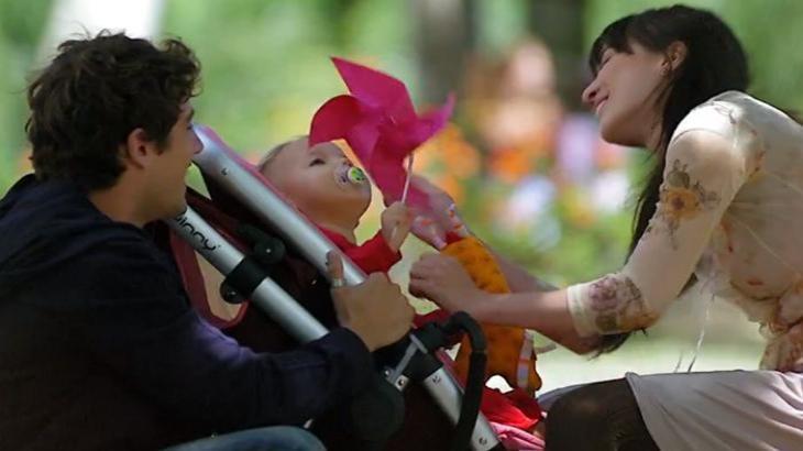 Cena de A Vida da Gente com Julia no carrinho de bebê, e Rodrigo e Manu frente a frente sorrindo