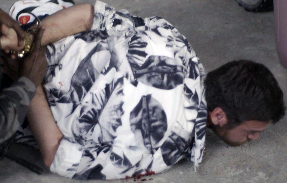Rubinho deitado no chão com as mãos para trás sendo algemado