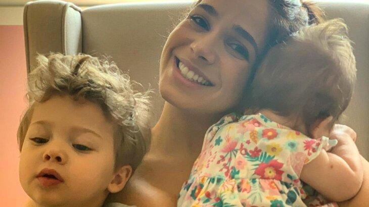 Sabrina Petraglia sorridente com os filhos, Gael e Maya, no colo