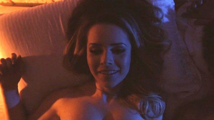 Sandy aparece de topless na cama em cena quente de novo clipe