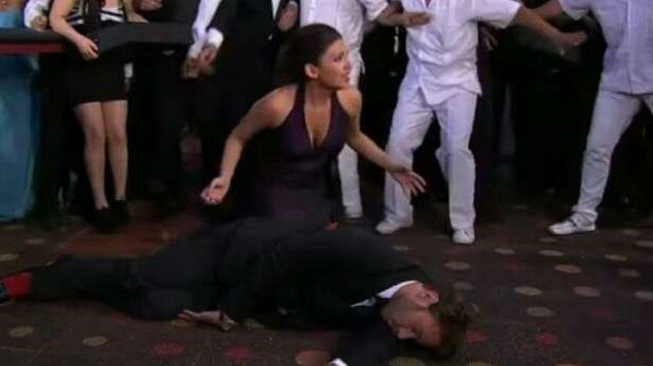 Cena de Coração Indomável com Karim caído e Maricruz ajoelhada ao seu lado