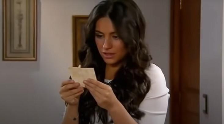 Cena de Coração Indomável com Maricruz em pé lendo um papel, que ela segura com sua mão