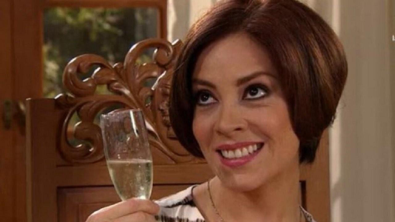 Cena de Coração Indomável com Simone sorrindo segurando uma taça de champanhe
