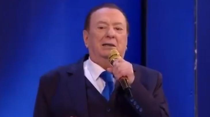 Raul Gil no palco do Programa Raul Gil, segurando o microfone e olhando para a câmera