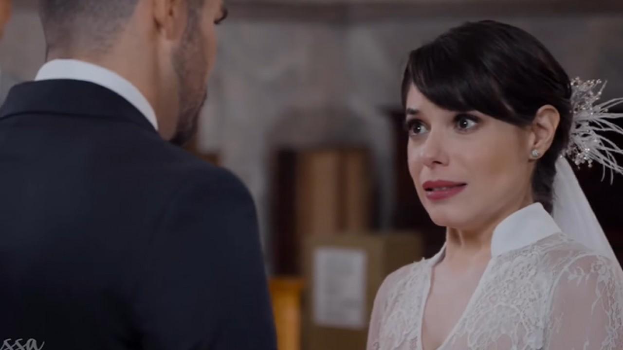 Cena de Te Dou a Vida com Gina chorando, vestida de noiva, e olhando para Pedro