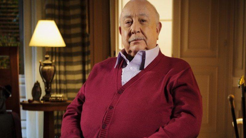 Sérgio Mamberti, de bigode, sentado com um casaco vinho