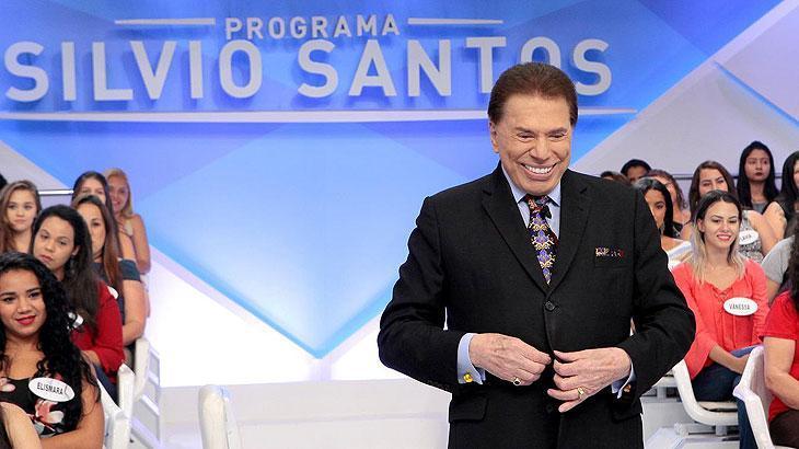 Silvio Santos com sua tradicional gargalhada abotoando o terno