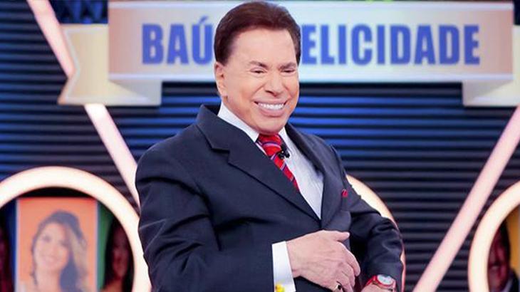 Silvio Santos no palco do SBT com mão na barriga