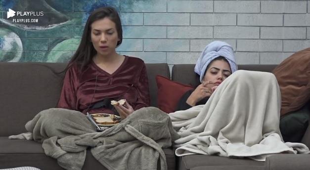 Stéfani Bays comendo de blusa vinho e Mirella de toalha na cabeça deitada