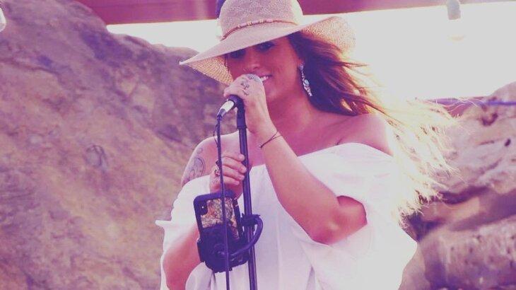 Taylor Dee cantando com microfone