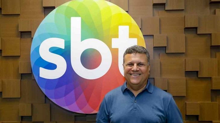 Téo José à frente do logotipo do SBT