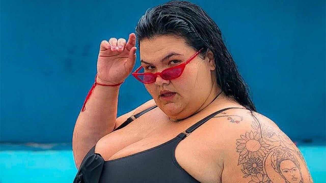 Thais Carla de maiô em piscina, com a mão levantada