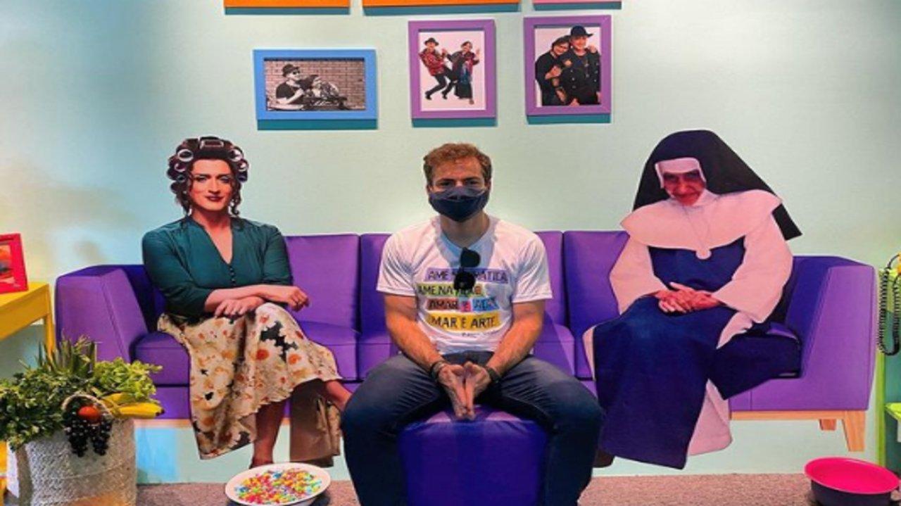 Thales Bretas sentado ao lado de imagem de Paulo Gustavo e Irmã Dulce