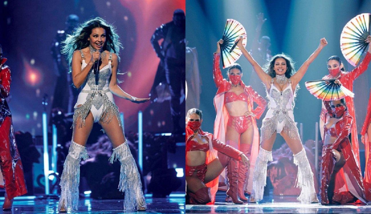 A cantora Thalía de maiô branco e botas durante show