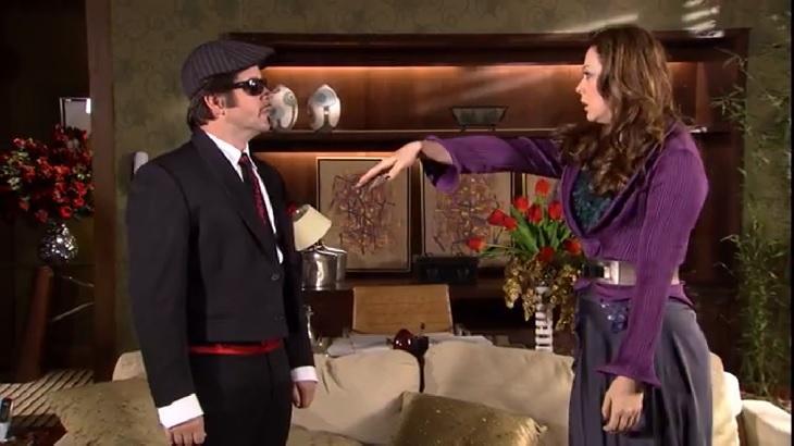 Cena de Ti Ti Ti com Jaqueline e Victor Valentim frente a frente e ela com a mão esticada para ele beijar