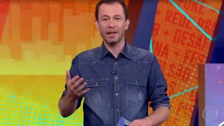 Tiago Leifert apresentando o BBB21 no estúdio do programa de camisa jeans