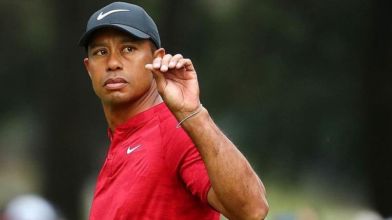 Tiger Woods de semblante sério fazendo sinal com a mão