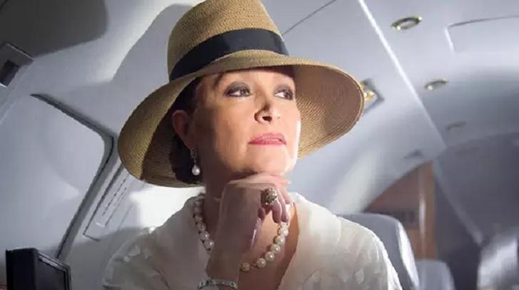 Cena de Triunfo do Amor com Bernarda num jatinho, usando chapéu, colar e com a mão no queixo