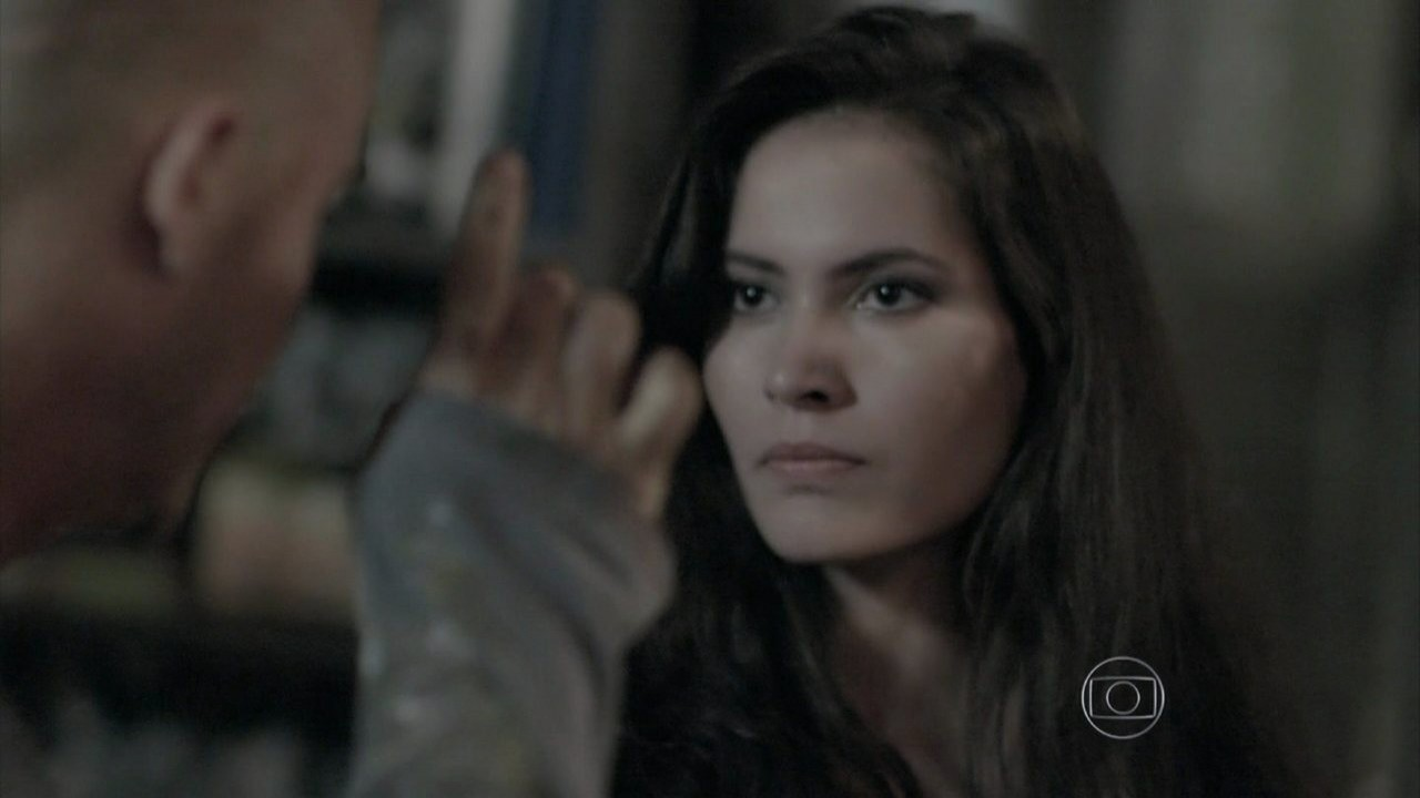 Salvador ameaçando Carmen enquanto ela o encara