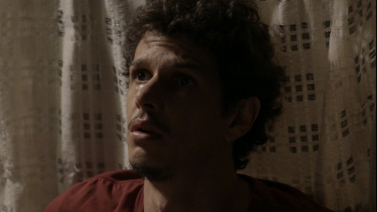 Elivaldo sentado no chão, enconstado à parede assustado