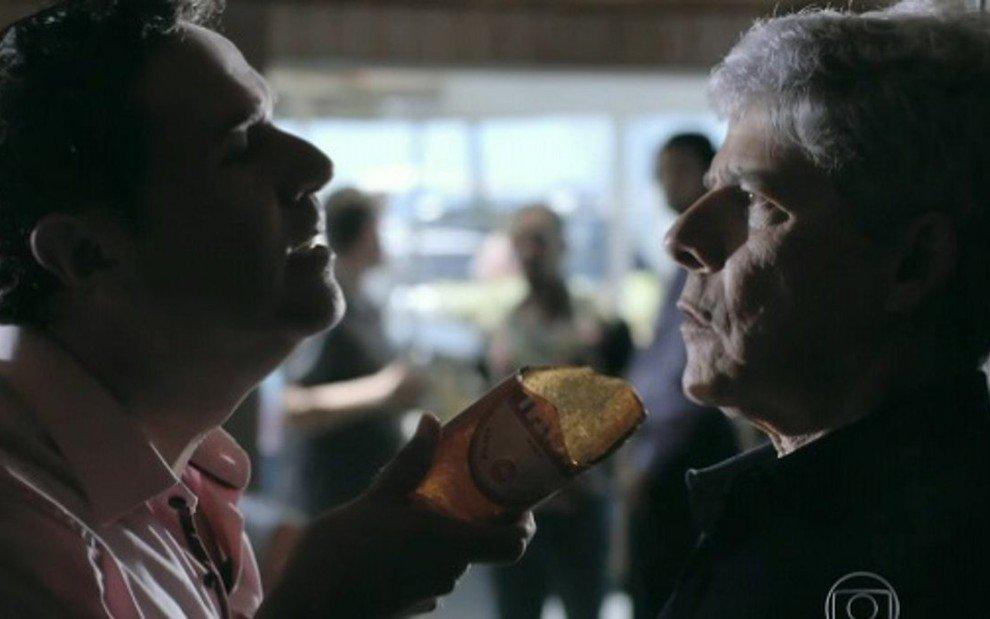 Felipe com uma garrafa de cerveja quebrada na direção da garganta de Cláudio