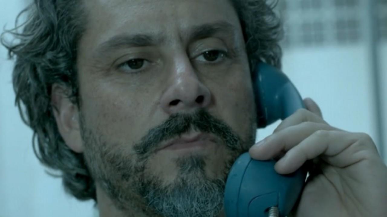 José Alfredo segurando o telefone no ouvido e expressão séria