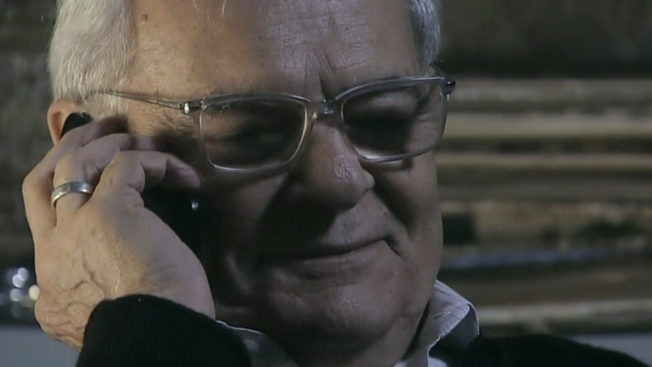 Silviano com sorriso cínico e o celular no ouvido