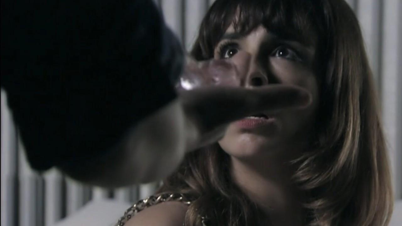 Danielle olha com espanto para Marílio segurando o diamante cor-de-rosa