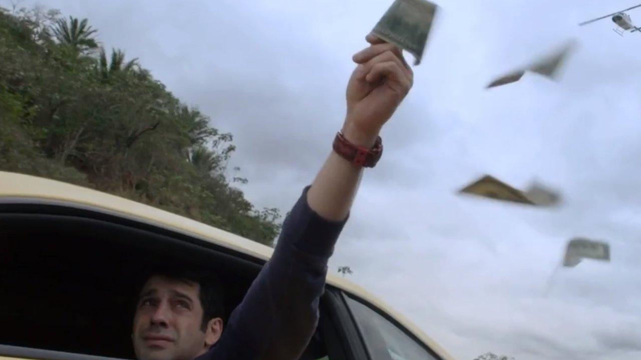 Agnaldo com a mão cheia de dólares pra fora do carro