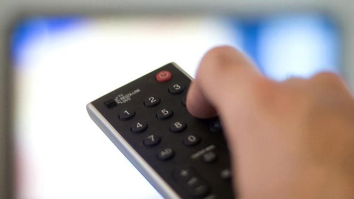 Foto de uma mão com controle remoto
