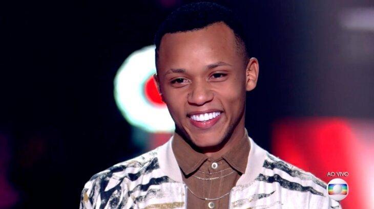 Victor Alves sorridente no palco do The Voice Brasil