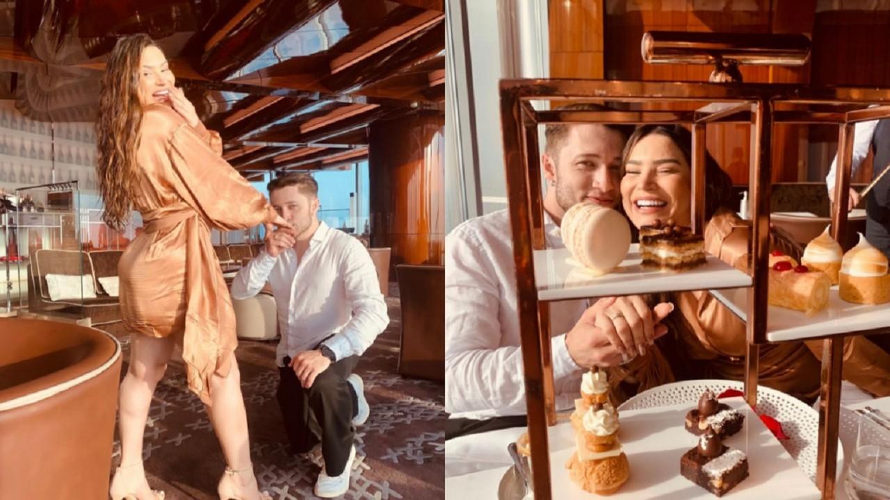 Raissa Barbosa ao lado de Victor Ferraz, ajoelhado, beijando a mão dela após noivado e os dois sentados e sorridentes em restaurante de Dubai