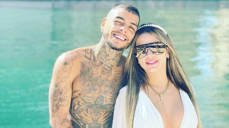 MC Kevin, sem camisa, e Deolane Bezerra, com óculos de sol, posados em barco