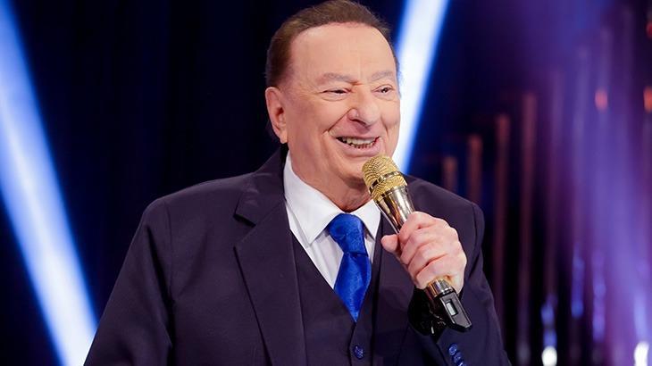 O apresentador Raul Gil sorridente segurando o microfone no palco do seu programa