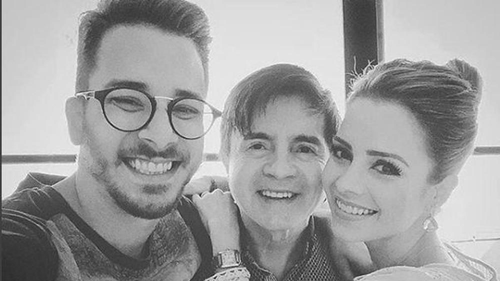 Em foto em preto e branco, Xororó aparece sorridente ao lado dos filhos, Sandy e Junior
