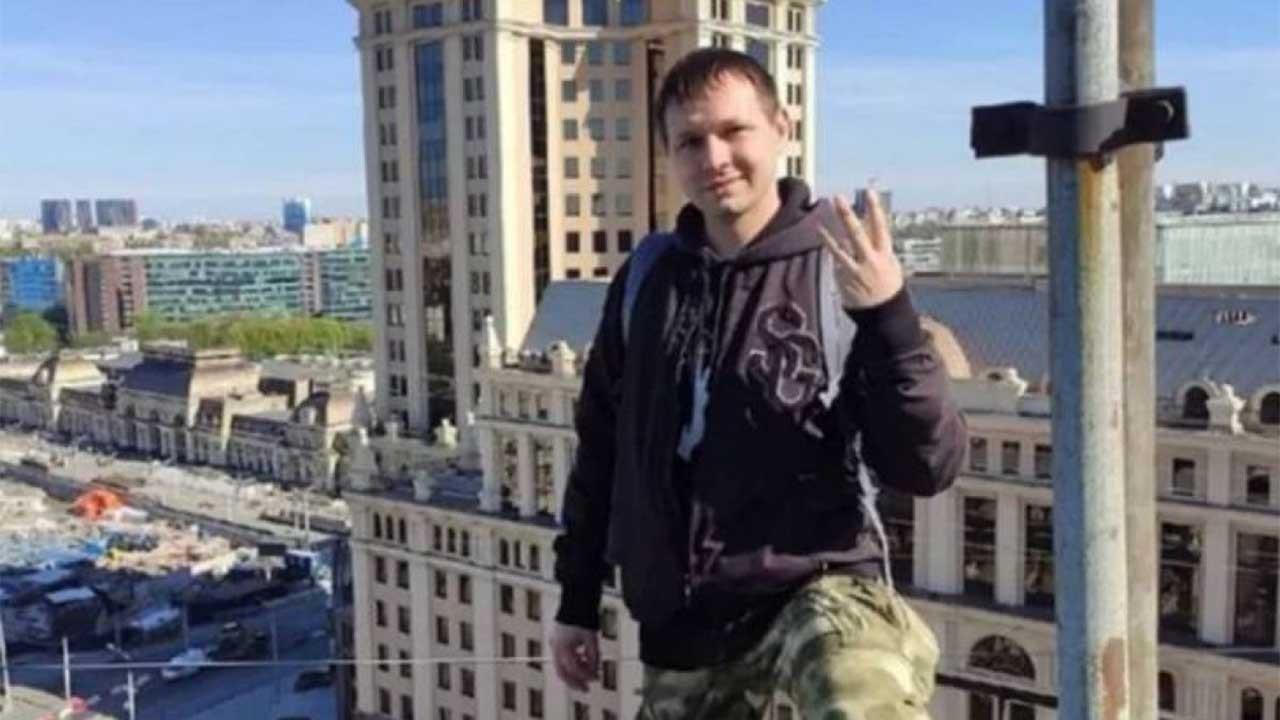 Dima Vert em cima de prédio, posado, mostrando três dedos