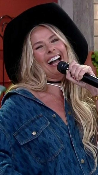 Adriane Galisteu sorrindo segurando microfone