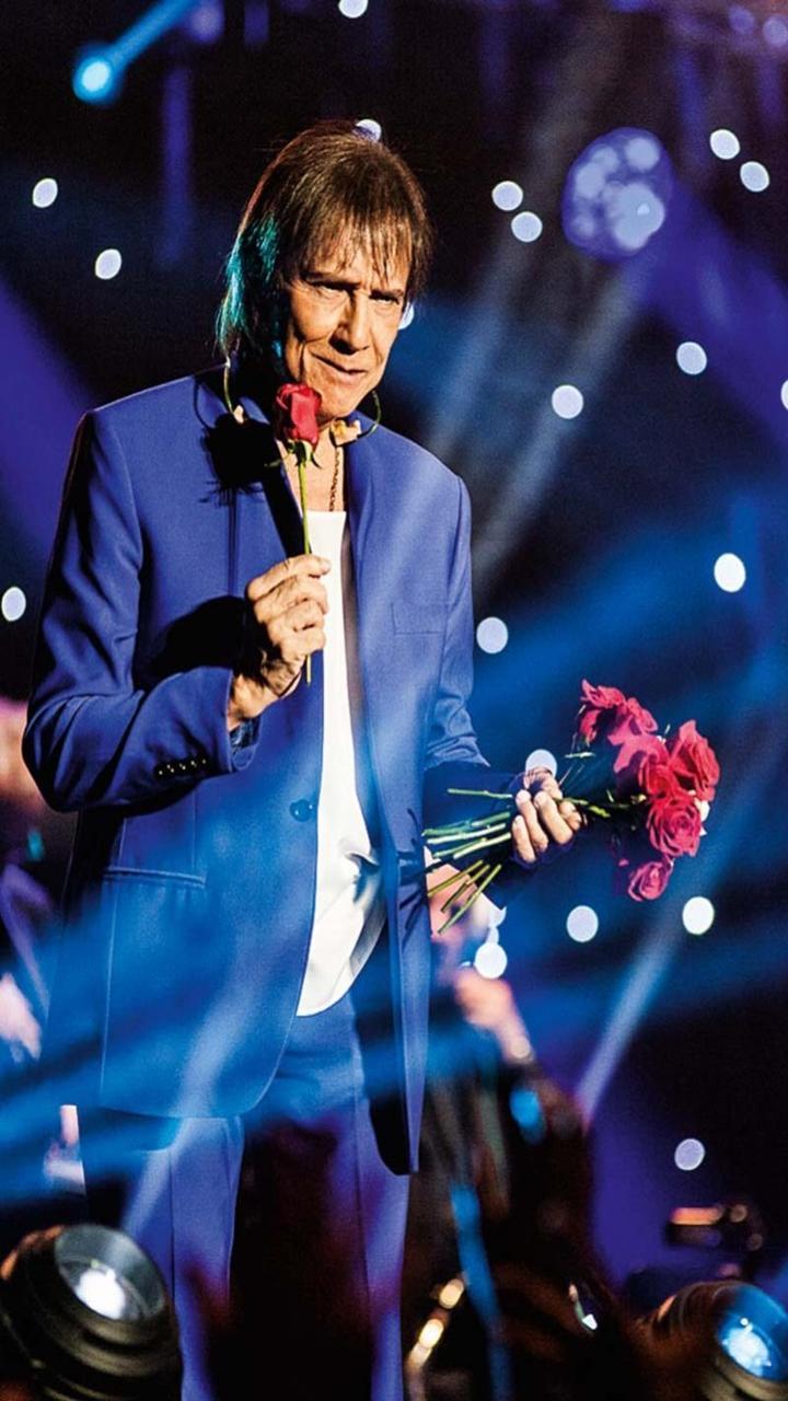 Roberto Carlos entregando rosas no show