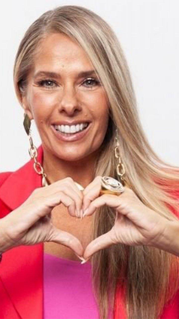 Adriane Galisteu fazendo coração com a mão, posada para foto